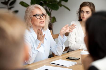 Attraktiver gealterter Geschäftsfrau-, Lehrer- oder Mentortrainer, der mit jungen Leuten, ältere Frau in den Gläsern unterrichtendes Publikum am Trainingsseminar, weiblicher Unternehmensleitersprecher spricht bei der Sitzung spricht