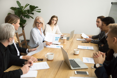 Serious aged businesswoman discussing corporate financial report with team talking to employees, senior mature female boss ceo leader analyzing work results with subordinates at company group meeting Stock Photo