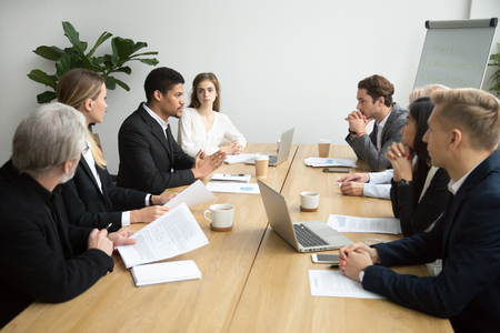Focused black team leader talking to colleagues at meeting sitting at conference table, serious african american executive manager presenting new business idea during group briefing or negotiations Stock Photo