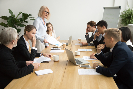 Dissatisfied senior woman boss scolding employees for bad work at diverse group meeting, angry female executive team leader reprimanding subordinates for poor financial result at office briefing Stockfoto