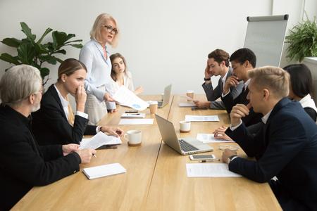 Unzufriedener älterer Frauenchef, der Angestellte für schlechte Arbeit an der verschiedenen Gruppensitzung, verärgerter weiblicher Exekutivteamleiter tadelt Untergebene für schlechtes Finanzergebnis an der Büroanweisung schilt Standard-Bild
