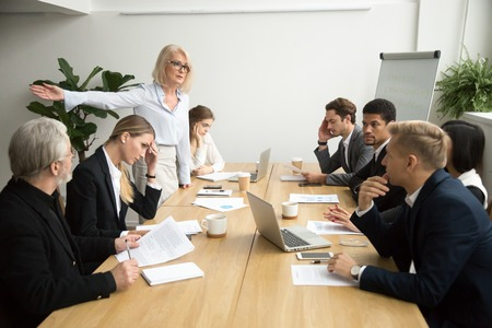 Angry senior woman boss firing unprofessional employee with hand gesture at diverse team meeting, dissatisfied aged female executive dismissing incompetent manager for bad work result in boardroom