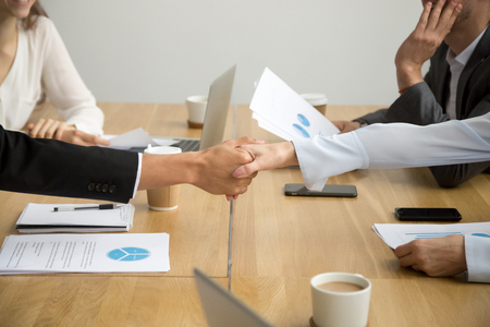 Diverse businessman and businesswoman handshaking at group meeting, close up view of white female and black male hands shaking as concept of gender equality racial diversity in business, making deal Stock Photo