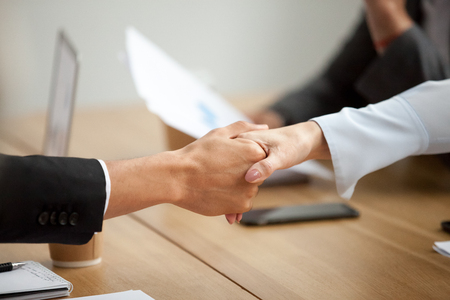 Multiracial businessman and businesswoman handshaking promising good deal at meeting, african man shaking hand of caucasian woman respecting gender equality or racial diversity concept, close up view Stock Photo