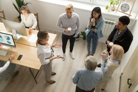 Team leaders meet multiracial interns in office explaining new job, company executives talking to diverse workers listening instructions at break, discussion and computer work in coworking, top view Stock Photo