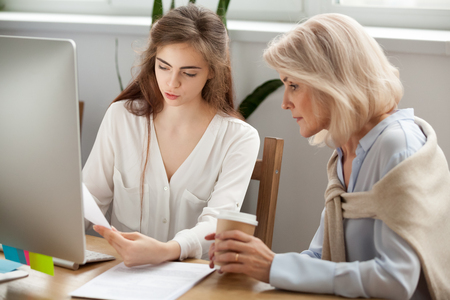 Young and older businesswomen discuss documents working together in office, manager explains senior woman contract details, colleague talking to executive showing report, conversation about paperwork