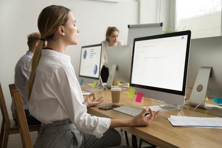 Giovane donna di affari pacifica calma che medita alla scrivania con gli occhi chiusi, responsabile degli impiegati della società che pratica yoga nel luogo di lavoro per equilibrio emotivo mentale, nessuno stress sul sollievo dal lavoro, vista laterale