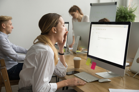 Tired businesswoman yawning working on computer sitting at desk with colleagues, sleepy employee gaping suffering from lack of sleep, feeling bored or chronic fatigue in office concept, side view Stock Photo