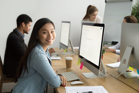 Smiling asian office employee looking at camera working with multiracial colleagues, happy young company manager sitting at corporate workplace, cheerful team member posing with desktop computer Stock Photo