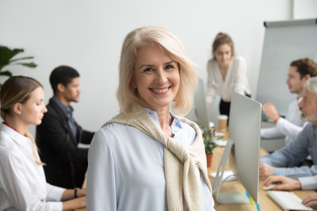Smiling female aged company executive or team leader looking at camera, happy senior businesswoman teacher coach posing with office people at background, friendly older woman boss head shot portrait Stockfoto