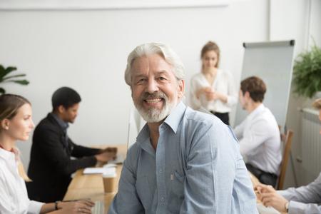 Lächelnder männlicher älterer Teamleiter, gealterter Lehrer, der Kamera mit Büroleuten am Hintergrund, am glücklichen alten grauhaarigen Firmenchef, am erfahrenen Mentor oder am Exekutivberufshauptschußporträt betrachtet