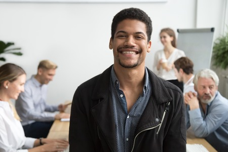Smiling african american office employee or leader looking at camera with diverse colleagues at background, happy young black manager, professional coach or team member posing, head shot portrait Imagens