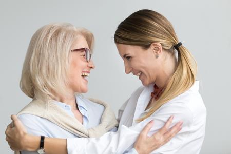 Glückliche ältere Mutter, welche die erwachsene Tochter zusammen lacht, lächelnde aufgeregte gealterte ältere Dame umarmt junge Frau, aufrichtige Familie von den verschiedenen Altersgenerationen umfasst, welche die Unterhaltung verpfänden, die Spaß habend scherzt Standard-Bild