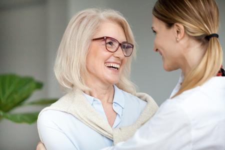 若い大人の女性を抱きしめ、笑うメガネをかけた美しい高齢の女性、大人の娘を抱きしめるのが嬉しい魅力的な先輩の母親に笑い、一緒に楽しんで 写真素材