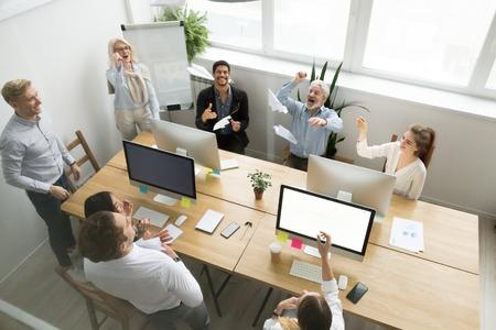 Groupe d'affaires heureux et diversifié de jeunes et seniors employés à lancer ensemble des avions en papier, activité de team building au bureau, nouveau projet, démarrage et concept de travail d'équipe, vue de dessus d'en haut