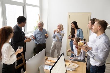 Friendly diverse business team of young and senior colleagues eating pizza together in office, multiracial coworkers staff group talking and laughing at funny joke on lunch time or coffee break