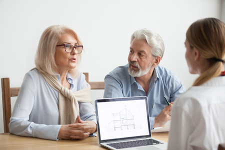 Senior couple talk to real estate agent about house purchase at meeting, interior designer advisor consulting older family with home plan on laptop screen, aged man and woman negotiating with realtor