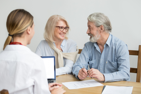 Happy senior couple deciding discussing new house purchase at meeting with agent, smiling older aged family consulting about buying home, taking mortgage loan, making investment or real estate deal Stock Photo