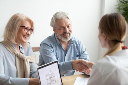 Die lächelnden erfüllten älteren Paare, die den Verkaufskauf abschließen, handeln die Immobilienagentur oder Grundstücksmakler, die glückliche ältere Familie und der Vermittler Händeschütteln, die zustimmen, neues Haus bei der Sitzung zu kaufen Standard-Bild