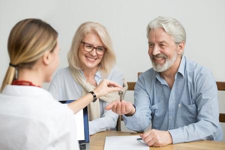 Gelukkig hoger paar krijgt sleutels van eigenaar van onroerend goed, opgewonden oudere klanten die onroerend goed kopen tijdens ontmoeting met agentconcept, glimlachende oude familie kopers blij om nieuwe huiseigenaren te worden