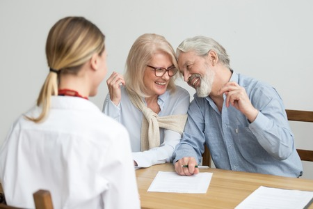 Loving caring senior aged couple laughing signing documents at meeting with financial advisor, happy older retired family investing savings in bank, making real estate deal, buying medical insurance