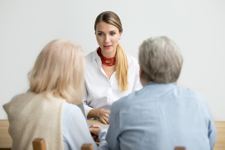 Female financial advisor consulting senior couple about making investment, insurance broker, realtor or travel agent talking to older family presenting new offer at meeting, woman at job interview