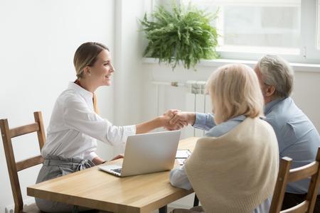 Der lächelnde weibliche Rechtsanwalt, die Immobilienagentur oder der Finanzberater, die ältere ältere Paare, der Versicherungsmakler und die gealterte Familie Händeschütteln Kaufabkommen, -investition oder -gruß bei der Sitzung abschließen