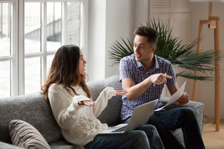 Young couple arguing about high domestic bills to pay with laptop and documents, unhappy family having conflict disagreement discussing unpaid debt or money problems sitting together on sofa at home Stock Photo