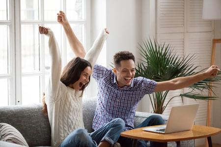Emocionado hombre y mujer gritando de alegría levantando las manos mirando la pantalla del portátil sentado en el sofá en casa, feliz pareja joven celebra en línea victoria victoria, logro de objetivos, buenas noticias, nueva oportunidad