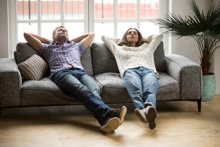Young couple relaxing having nap or breathing fresh air, relaxed man and woman enjoying rest on comfortable sofa in living room, happy family leaning on soft couch taking break for dozing together Banque d'images