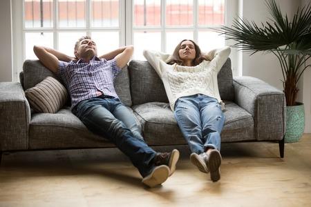 Młoda para relaksująca się, drzemiąc lub oddychając świeżym powietrzem, zrelaksowany mężczyzna i kobieta odpoczywają na wygodnej sofie w salonie, szczęśliwa rodzina opierając się na miękkiej kanapie, robiąc sobie przerwę na drzemkę Zdjęcie Seryjne