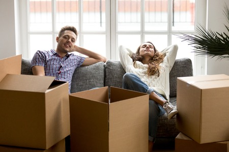 Happy couple relaxing on couch after moving in new home, smiling young husband and wife homeowners or tenants taking break for rest together while packing unpacking cardboard boxes relocating concept Stock Photo