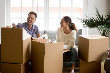 Happy couple having fun and laughing while unpacking boxes on moving day, smiling young family packing sorting belongings in modern living room settle in new home or preparing for relocation concept Stock Photo