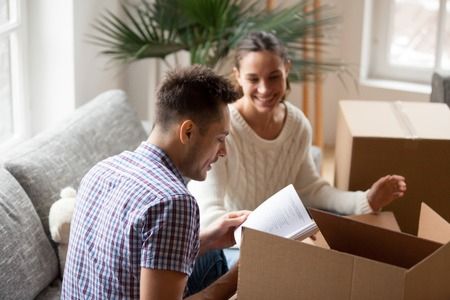 Young man holding book helping wife to pack cardboard boxes on moving day, smiling young couple unpacking sorting belongings settle in new home, family preparing for relocation together concept Archivio Fotografico