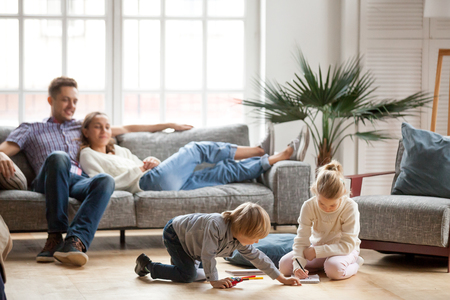 Niños hermana y hermano jugando a dibujar juntos en el piso mientras los padres jóvenes se relajan en casa en el sofá, la niña se divierte, la amistad entre hermanos, el tiempo libre en la sala de estar familiar