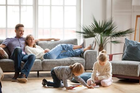 Siostra i brat dzieci bawiące się, rysując razem na podłodze, podczas gdy młodzi rodzice relaksują się w domu na kanapie, mała dziewczynka bawi się, przyjaźń między rodzeństwem, rodzinny czas wolny w salonie