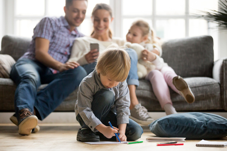 Serious cute son holding color marker drawing on floor while parents with sister sitting apart, preschool kid loner boy playing alone, family leisure at home and creative child development concept