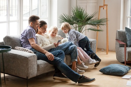 Happy family with children using mobile apps together at home, young couple and kids having fun playing game on smartphone sitting on sofa, parents and son daughter relaxing in living room with phone Stock Photo