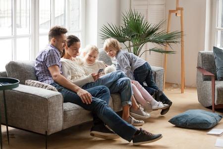 Szczęśliwa rodzina z dziećmi korzystającymi razem z aplikacji mobilnych w domu, młoda para i dzieci bawiące się grając w grę na smartfonie siedząc na kanapie, rodzice i syn córka relaksująca się w salonie z telefonem