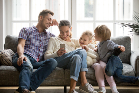 一緒にソファに座ってスマートフォンで面白いビデオを見て笑う子供たちと陽気な若い家族、自宅で携帯電話で携帯電話を使用してゲームを楽しむ