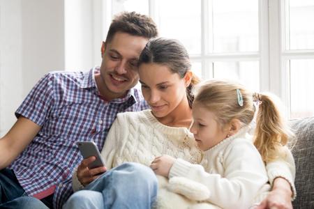 딸이 집에서 휴대 전화로 비디오를보고, 교육을 위해 응용 프로그램을 사용하거나 소셜 네트워크를 확인하는 어린 소녀와 함께 젊은 가족 커플 소파에 앉아 스마트 폰에 초점을 맞춘 부모 스톡 콘텐츠 - 98318592