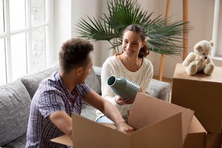 Pareja sonriente empacando cajas de cartón juntos sentados en el sofá en la sala de estar preparándose para reubicarse, joven mujer feliz sosteniendo el jarrón ayudando al hombre a desempacar pertenencias en movimiento en el nuevo concepto de hogar