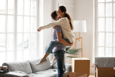 Excited couple celebrating moving day, man lifting embracing happy woman standing among boxes glad to move into new house, husband hugging delighted wife enjoying relocation starting living together