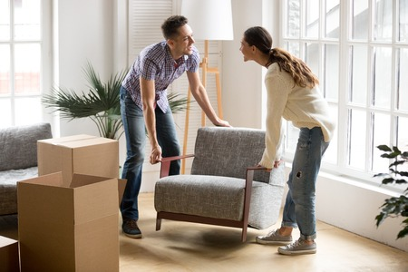 Smiling couple carrying modern chair together placing furniture moving into new home, young family discussing house improvement interior design while furnishing living room, remodeling and renovation Stock Photo