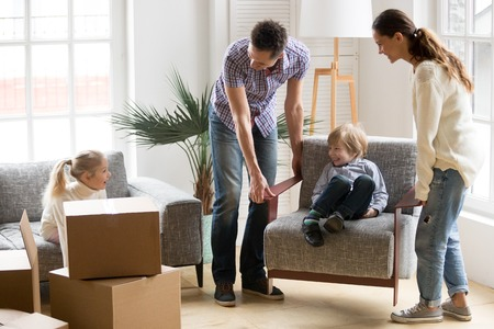 Happy young family with small kids having fun together playing on moving day in new home concept, father and mother carry little son on chair while excited daughter sitting on sofa unpacking boxes Stock Photo