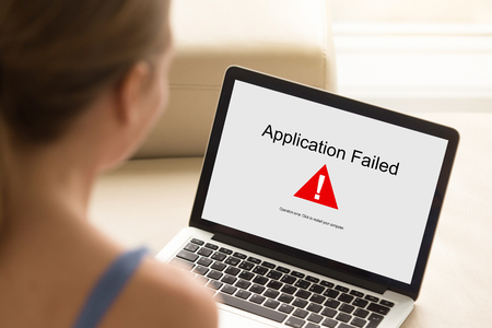 Girl looking at laptop with Application Failed error on screen. Software failure, app stopped working, computer unit broke, system crashed unexpectedly, malware concept. Close up, focus on screen. Stock Photo