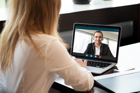 Empresaria que hace videollamada al socio comercial que usa la computadora portátil. Vista posterior del primer de la mujer joven que tiene discusión con el cliente corporativo. Entrevista de trabajo remota, consulta, concepto de recursos humanos.