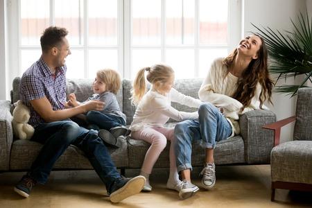 Szczęśliwi rodzice i dzieci bawią się łaskotaniem siedząc razem na kanapie, wesoła para śmiejąca się grając w grę z małym aktywnym synem i córką w salonie w domu, zabawna aktywność rodzinna
