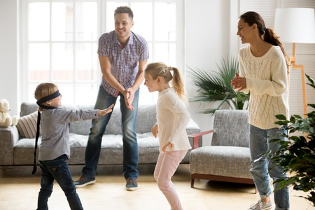 Con los ojos vendados, lindo niño jugando al escondite en casa, padres e hijos riendo pasando tiempo juntos disfrutando del juego el fin de semana, feliz familia de cuatro divirtiéndose en la sala de estar. Foto de archivo