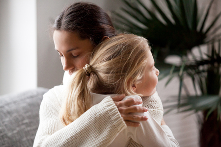 Loving mother hugging cute little girl, young woman embracing adopted child holding tight, sincere warm relationships between mum and daughter cuddling, moms love and care or adoption concept Stock Photo